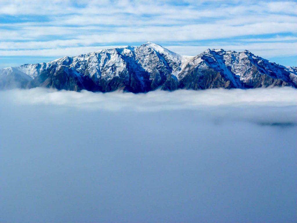 Gipfel hinter der Wolkendecke über Lake Hawea
