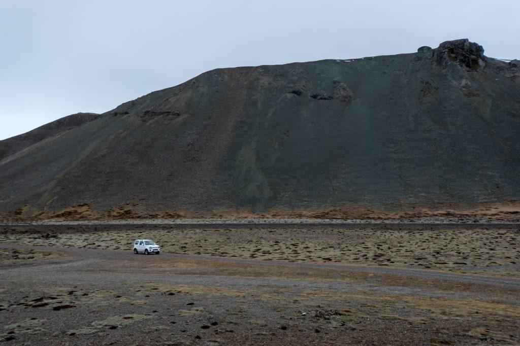 Der kleine Mietwagen vor den mächtigen Lava Bergen
